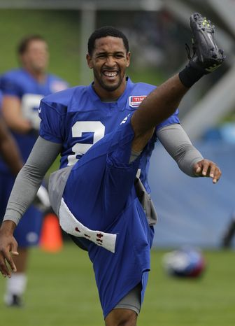 CORRECTS NAME OF PLAYER TO TERRELL THOMAS -- New York Giants cornerback Terrell Thomas does a high kick while warming up before a workout at the New York Giants NFL football training camp in Albany, N.Y., Sunday, July 29, 2012. (AP Photo/Kathy Willens)