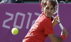 Roger Federer of Switzerland returns to John Isner of the United States at the All England Lawn Tennis Club in Wimbledon, London at the 2012 Summer Olympics, Thursday, Aug. 2, 2012. (AP Photo/Elise Amendola)
