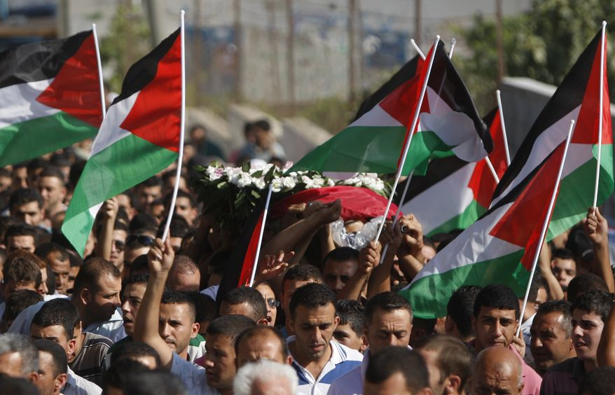 **FILE** Palestinian mourners carry the body of Akram Badr, 46, during his funeral July 31, 2012, in the village of Beitillu near in the West Bank city of Ramallah. Badr was killed the previous day at a checkpoint by the Israeli security forces near Jerusalem. (Associated Press)