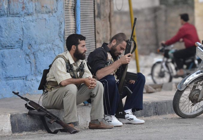 Free Syrian Army soldiers sit on a sidewalk at the northern town of Sarmada, in Idlib province, Syria, Wednesday, Aug. 1, 2012. (AP Pho