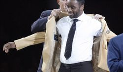 Curtis Martin receives his gold jack from presenter Bill Parcells at the Enshrinees' Gold Jacket Dinner at the Memorial Civic Center on Friday, Aug. 3, 2012, in Canton, Ohio. Martin will be enshrined in the Pro Football Hall of Fame on Saturday. (AP Photo/The Repository, Scott Heckel)