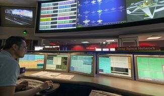 ** FILE ** This Aug. 2, 2012, file photo shows Nick Lam, data controller, monitoring the Mars rover Curiosity from the Deep Space Network's control room at NASA's Jet Propulsion Laboratory in Pasadena, Calif. (AP Photo/Damian Dovarganes, File)