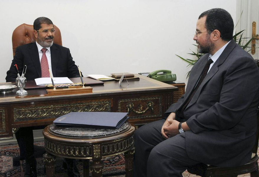 ** FILE ** In this Sunday, July 22, 2012, file photo released by the Egyptian Presidency, Egyptian President, Mohammed Morsi, left, meets with the minister of Water Resources and Irrigation, Hesham Kandil, at the Presidential Palace in Cairo. (AP Photo/Ahmed Mourad, Egyptian Presidency, File)