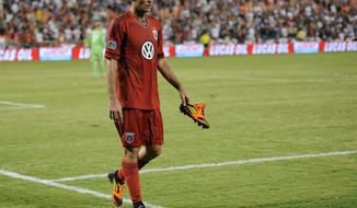 D.C. United defender Emiliano Dudar (19) walks with his cleat in his hand towards the bench during the second half of an international friendly soccer game in the World Football Challenge against Paris Saint-Germain, Saturday, July 28, 2012, in Washington. The game ended in a 1-1 tie. (AP Photo/Nick Wass)