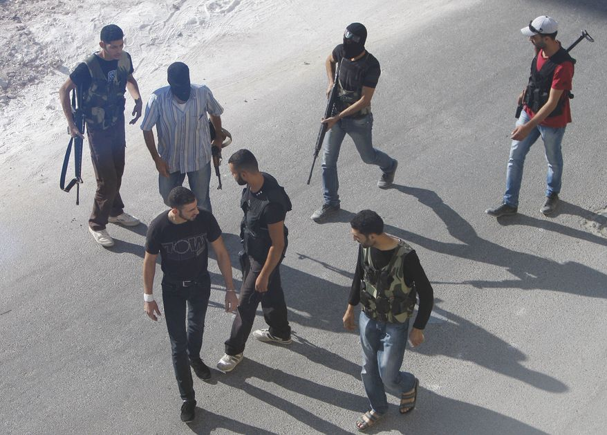 In this Thursday Aug. 2, 2012 photograph, Syrian rebel fighters man an improvised checkpoint in a suburb of Damascus, Syria. (AP Photo)