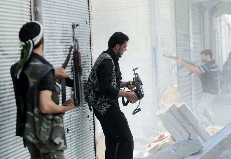 A Free Syrian Army soldier fires his weapon during clashes with Syrian government forces in the Saladin neighborhood in Aleppo, Syria, on Wednesday. An activist in Damascus said rebels are increasingly using a tactic of quick-hit attacks to frustrate security forces and keep the capital and other locations unstable. (Associated Press)