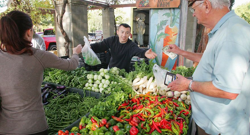 Richard Wolk buys fresh produce from Ching Thao at the Vineyard Farmers Market in California, a state that is leading the way in direct-sales markets. (Associated Press)