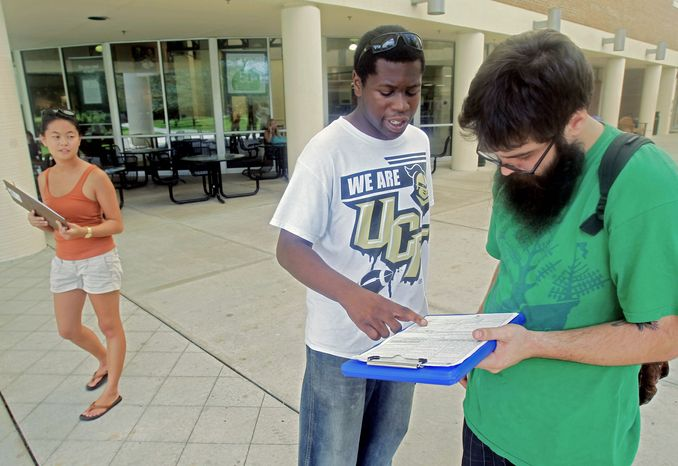 Aubrey Marks (left) looks on Tuesday at the University of Central Florida in Orlando, Fla., as Jordan Allen (center) helps student Casey Eirhstaedt register to vote. While most college campuses are relatively quiet, students at UCF have taken it upon themselves to register peers during the summer. (Associated Press)