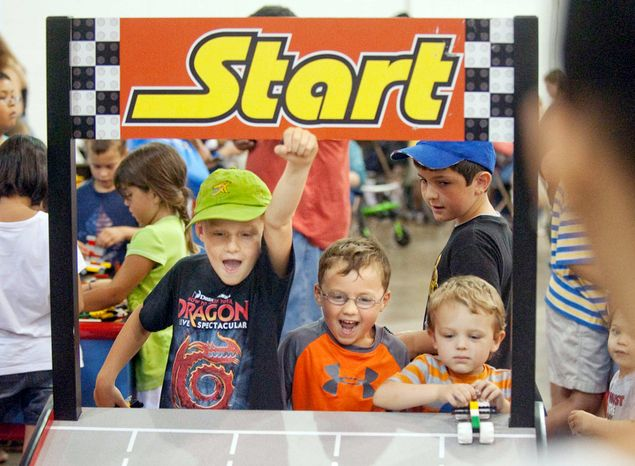 Griffin Brown, 8, and Hudson Brown, 6, both from Chevy Chase Md., celebrate after racing their Lego cars during the Brickfair Lego Convention. (Raymond Thompson/The Washington Times)