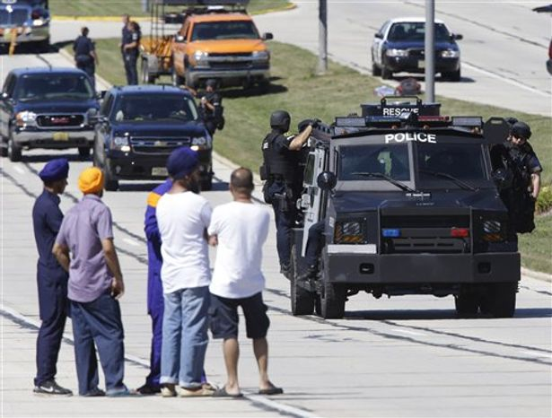 People watch police personnel outside the Sikh Temple in Oak Creek, Wis., where a shooting took place on Sunday, Aug 5, 2012. (AP Photo/Jeffrey Phelps)