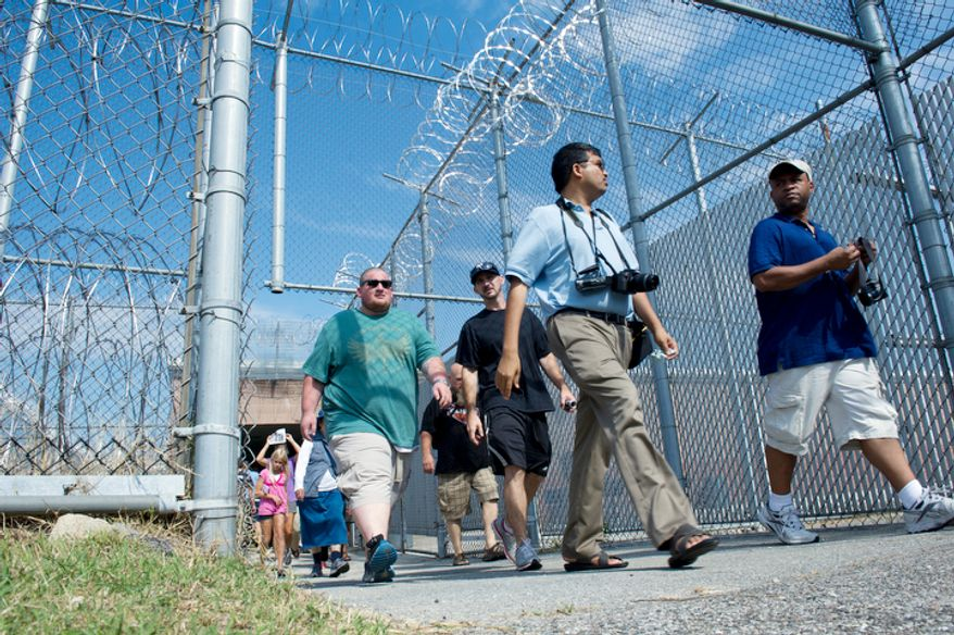 People walk through a barbed-wire gated area to enter the Maryland House of Corrections in Jessup, Md during an open house on Sunday, Aug. 5, 2012.  (Barbara L. Salisbury/The Washington Times)