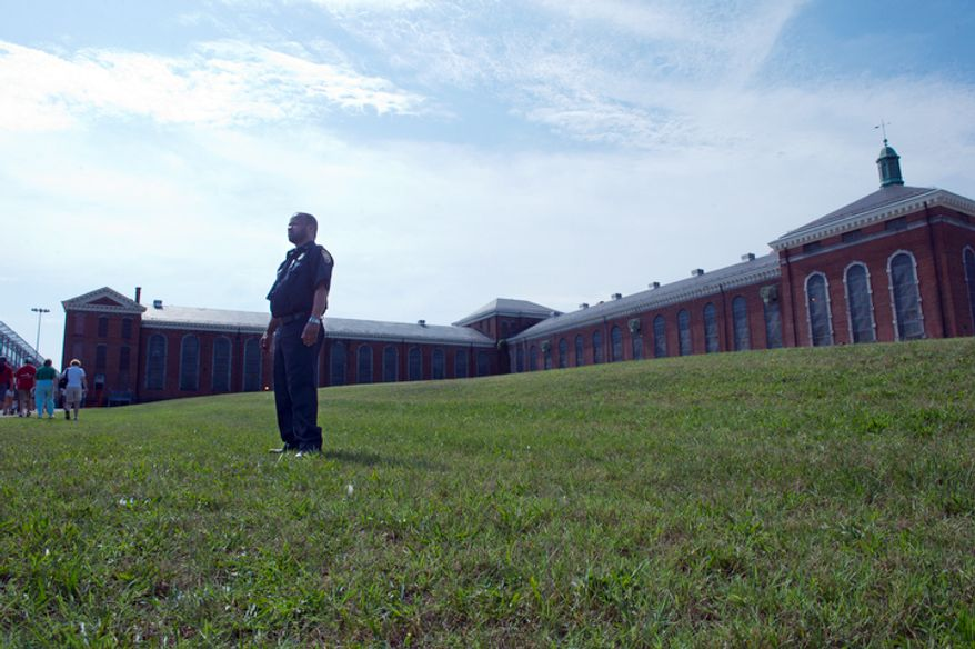 Corrections Officer Anthony Smith stands guard outside the Maryland House of Corrections in Jessup, Md., as the general public walks up to the facility, following the same path a visitor visiting an inmate would have followed, during an open house.  (Barbara L. Salisbury/The Washington Times)