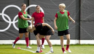 United States' Megan Rapinoe, right, warms up alongside teammates during a women's soccer training session for the 2012 London Summer Olympics, Sunday, Aug. 5, 2012 in Manchester, England. (AP Photo/Jon Super)