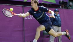 Andy Murray of Great Britain returns to Roger Federer of Switzerland during the gold medal men's singles match at the All England Lawn Tennis Club in Wimbledon, London, at the 2012 Summer Olympics, Sunday, Aug. 5, 2012. (AP Photo/Elise Amendola)