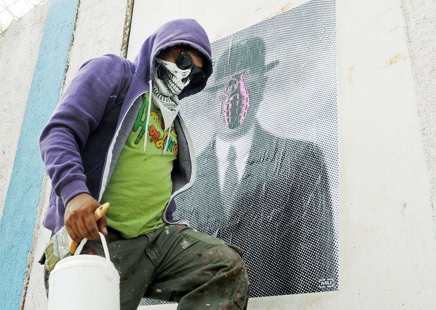 "In this July 29, 2012 photo, a masked artist who calls himself the Urban Maeztro and prefers to remain anonymous for security reasons, walks away after pasting one of his ""interventions"" on a street wall showing Rene Magritte's ""Son of Man,"" substituting the apple covering the face of the suited subject in bowler hat with a pink grenade, in Tegucigalpa, Honduras. The 26-year-old graphic artist left his day job at an advertising agency to work on pieces like this one, to encourage Hondurans think about how violent their country has become. (AP Photo/Fernando Antonio)"