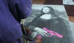 "In this July 29, 2012 photo, an artist who calls himself the Urban Maeztro and prefers to remain anonymous for security reasons, works on a black-and-white reproduction of Leonardo da Vinci's ""Mona Lisa"" holding a pink gun at his studio before hanging it in a public space in Tegucigalpa, Honduras. The 26-year-old graphic artist left his day job at an advertising agency to work on pieces like this one, to encourage Hondurans think about how violent their country has become. (AP Photo/Fernando Antonio)"