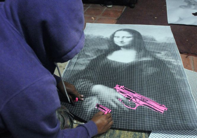 """In this July 29, 2012 photo, an artist who calls himself the Urban Maeztro and prefers to remain anonymous for security reasons, works on a black-and-white reproduction of Leonardo da Vinci's """"Mona Lisa"""" holding a pink gun at his studio before hanging it in a public space in Tegucigalpa, Honduras. The 26-year-old graphic artist left his day job at an advertising agency to work on pieces like this one, to encourage Hondurans think about how violent their country has become. (AP Photo/Fernando Antonio)"""