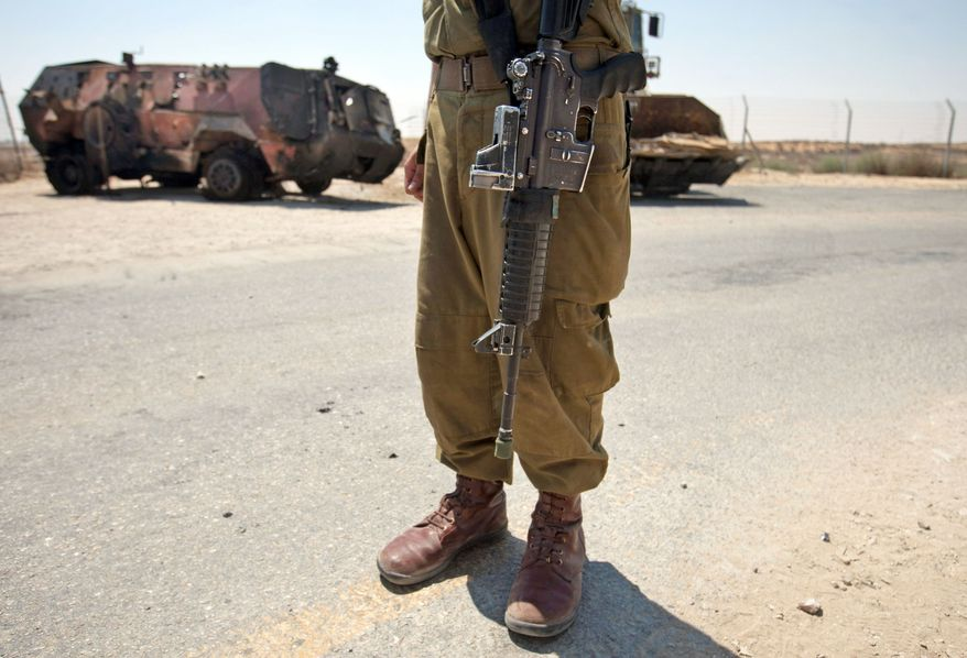 **FILE** An Israeli soldier examines the wreckage of an Egyptian military vehicle after militants drove it through a security fence into Israel from Egypt at an Israeli military base on Aug. 6, 2012. (Associated Press)