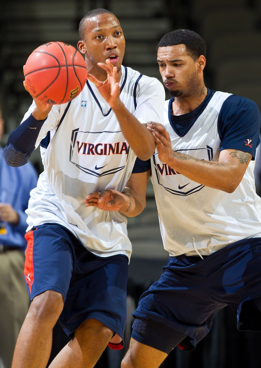 Virginia's Akil Mitchell, left, passes the ball while under pressure from Mike Scott during practice at the Century Link Arena in Omaha, Neb., Thursday, March 15, 2012. Virginia plays against Florida on Friday in an NCAA second-round tournament college basketball game. (AP Photo/The Omaha World-Herald/Rebecca S. Gratz)  MAGS OUT; ALL NEBRASKA LOCAL BROADCAST TV OUT