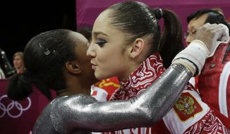 U.S. gymnast Gabrielle Douglas, left, congratulates Russia's Aliya Mustafina for winning the gold for the uneven bars during the artistic gymnastics women's apparatus finals at the 2012 Summer Olympics, Monday, Aug. 6, 2012, in London. (AP Photo/Julie Jacobson)