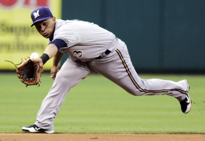**FILE** Milwaukee Brewers shortstop Cesar Izturis fields a line drive hit by Philadelphia Phillies' Jimmy Rollins to end the second inning of the Phillies' 7-6 home win on July 23, 2012. (Associated Press)
