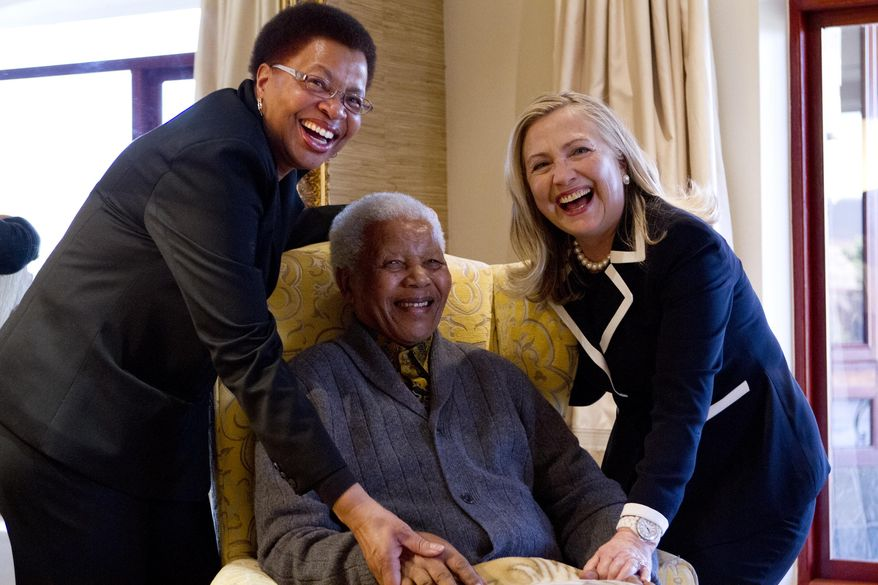 Secretary of State Hillary Rodham Clinton meets Aug. 6, 2012, with former South Africa President Nelson Mandela and his wife Graca Machel at his home in Qunu, South Africa. (Associated Press)