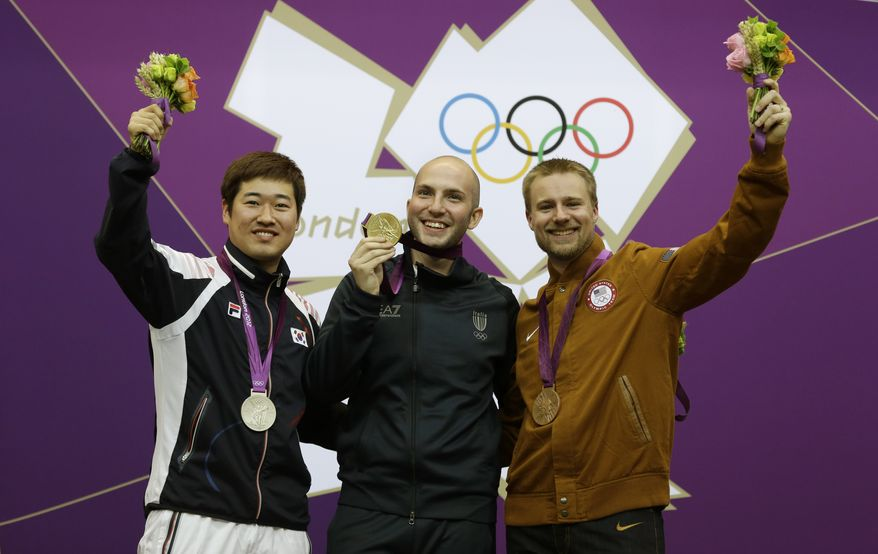 Gold medal winner Italy's Niccolo Campriani, center, poses for a picture with silver medalist Kim Jonghyun of South Korea, left, and bronze medalist Matthew Emmons of the United States of America, during the victory ceremony for the men's 50-meter rifle 3 positions event, at the 2012 Summer Olympics, Monday, Aug. 6, 2012, in London. (AP Photo/Rebecca Blackwell)
