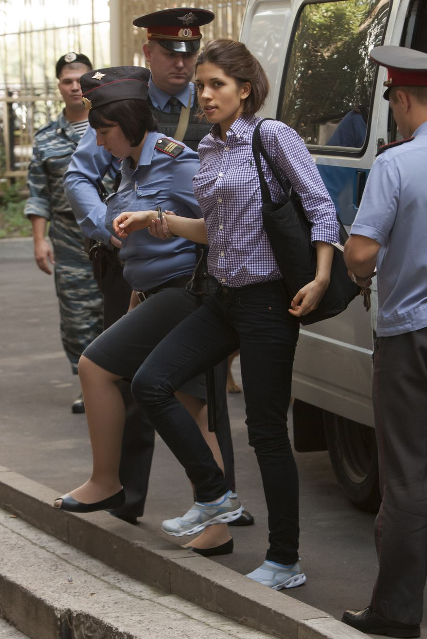 """Nadezhda Tolokonnikova (center), a member of the feminist punk group Pussy Riot, is escorted Aug. 6, 2012, to a courtroom in Moscow. Tolokonnikova and two other members of the group are facing trial on charges of hooliganism for performing a """"punk prayer"""" at Moscow's main cathedral against Vladimir Putin's return to the Russian presidency. (Associated Press)"""