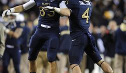 Navy's John O'Boyle, left, and Bo Snelson celebrate after their teammates stopped Army on fourth down in the second half of an NCAA college football game in Landover, Md., Saturday, Dec. 10, 2011. Navy won 27-21. (AP Photo/Nick Wass)