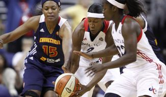 Connecticut Sun forward Asjha Jones, left, fights Washington Mystics center Michelle Snow, center, and guard Matee Ajavon for the ball during the first half of a WNBA basketball game on Friday, June 29, 2012, in Washington.  (AP Photo/ Evan Vucci)