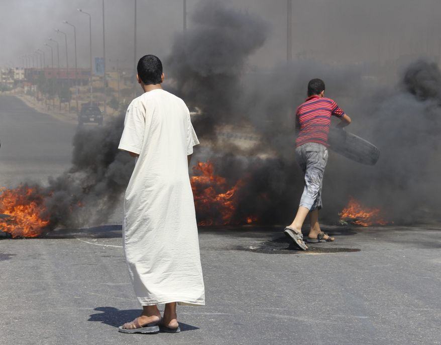 Angered by the attack Sunday evening that left at least 16 on Egyptian soldiers dead, residents of Rafah protest by burning tires in the road on the outskirts Rafah, Egypt, Monday, Aug. 6, 2012. (AP Photo)