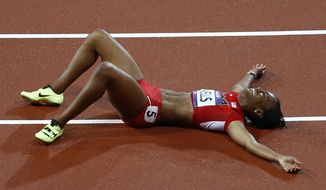 United States' Kellie Wells reacts after finishing third in the women's 100-meter hurdles during the athletics in the Olympic Stadium at the 2012 Summer Olympics, London, Tuesday, Aug. 7, 2012. (AP Photo/Daniel Ochoa De Olza)