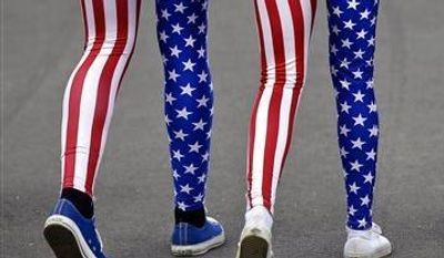 Nick Miller, left, and his sister Kendall Miller, center, from San Francisco, wear leotards in the colors of the United States national flag as they walk with a friend through Olympic Park at the 2012 Summer Olympics, in London. Patriotism and the games have always gone together, but gone are the days when one just waved a flag. Now flags are worn, seen all over London and especially at Olympic Park and other spots where the games are being played. (Associated Press)