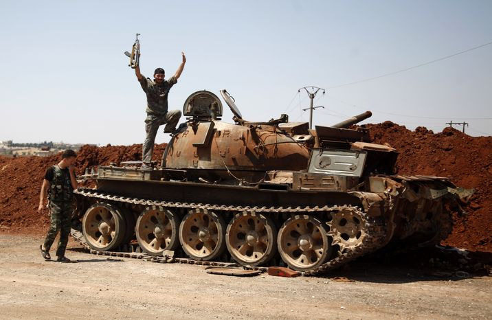 A Free Syria Army fighter waves Aug. 6, 2012, from the top of a destroyed army tank in the town of Anadan on the outskirts of Aleppo, Syria. (Associated Press)