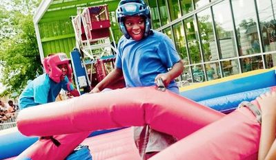Michael Briscoe, 10,  is loses his position during a jousting match at the Seven District's National Night Out at Anacostia Public Library on Tuesday, August 7, 2012, in Washington D.C. (Raymond Thompson/The Washington Times)