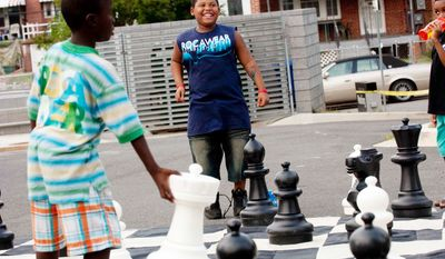 Kyree Wise, 9, plays a game of chess during the Seven District's National Night Out. Wise learned his chess skills from Blackanized INC, a organization that teaches chess and other life skills to young boys.(Raymond Thompson/The Washington Times)