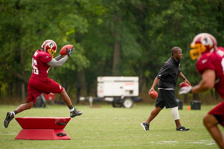 Washington Redskins defensive back Josh Wilson (26) runs a drill for Washington Redskins defensive back coach Raheem Morris, second from right, during afternoon practice at training camp at Redskins Park, Ashburn, Va., Tuesday, August 7, 2012. (Andrew Harnik/The Washington Times)