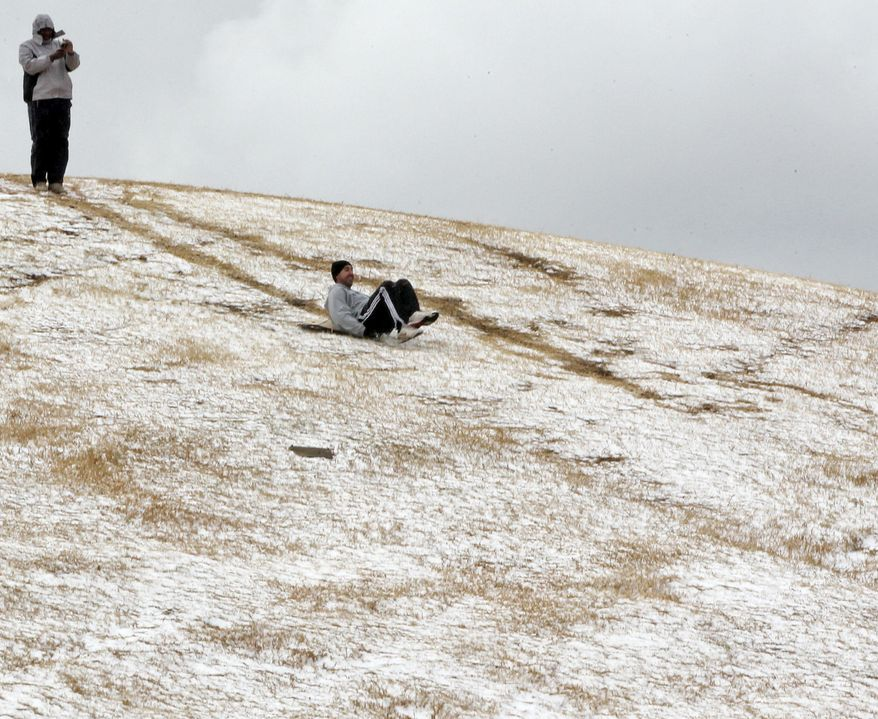 A man slides down a hill after a rare snowfall in Johannesburg on Tuesday sent people pouring out of their offices. The South African Weather Service said snow last fell in the city in June 2007. (Associated Press)