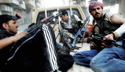 Free Syrian Army soldiers hold their weapons during clashes with government forces in the southwest district of Salah al-Din in Aleppo, Syria, last week. Syrian troops launched a ground assault Wednesday on the besieged northern city of Aleppo, but activists said rebels were fighting back in a battle for the city. (Associated Press)