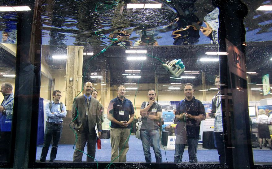 Fabian Paques operates a Seaperch drone, one of the robots, gadgets and commercial applications on display at the Unmanned Vehicle Systems International convention in Las Vegas. (Sam Morris/Special to The Washington Times)