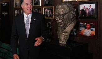 Republican presidential candidate Mitt Romney poses Aug. 7, 2012, with a bust of famed baseball announcer Harry Caray after a private fundraising event at Harry Caray's Italian Steakhouse restaurant in Chicago. (Associated Press)