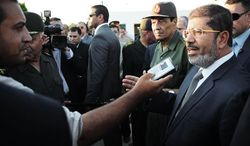 In this Sunday, Aug. 6, 2012 image released by the Egyptian President, Egyptian President Mohammed Morsi, right, speaks to the media as Field Marshal Gen. Hussein Tantawi, second right, listens during their visit to El Arish, Egypt's northern Sinai Peninsula. (AP Photo/Egyptian Presidency)