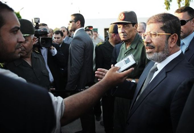 In this Sunday, Aug. 6, 2012 image released by the Egyptian President, Egyptian President Mohammed Morsi, right, speaks to the media as Field Marshal Gen. Hussein Tantawi, second right, listens during their visit to El Arish, Egypt&#39