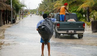 Police evacuate residents in Mahahual, Mexico, on Tuesday, Aug. 7, 2012, as Hurricane Ernesto bore down on the Caribbean coast. (AP Photo/Israel Leal)