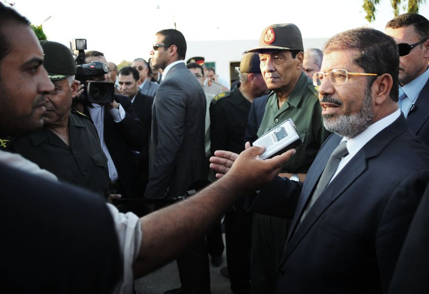 Egyptian President Mohammed Morsi (right) speaks to the media as Field Marshal Gen. Hussein Tantawi (second from right) listens during their visit to El Arish, in Egypt's northern Sinai Peninsula, on Sunday, Aug. 5, 2012. 