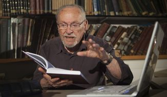 Prof. Menachem Cohen, a biblical scholar, reads July 31, 2012, from a book at the library of Bar Ilan University outside Tel Aviv. (Associated Press)