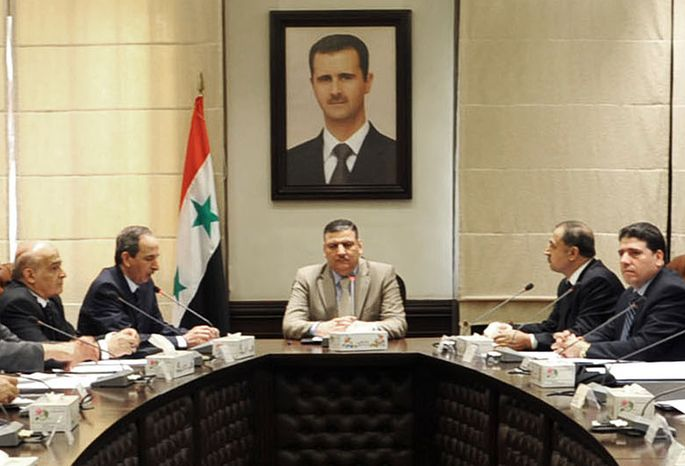 Then-Syrian Prime Minister Riad Hijab (center) speaks under the portrait of the Syrian President Bashar Assad during a meeting in Damascus, Syria, in an undated photo released by the official SANA news agency on Sunday, Aug. 5, 2012. Mr. Hijab has defected and fled to neighboring Jordan, a Jordanian official and a rebel spokesman said Monday. (AP Photo/SANA)