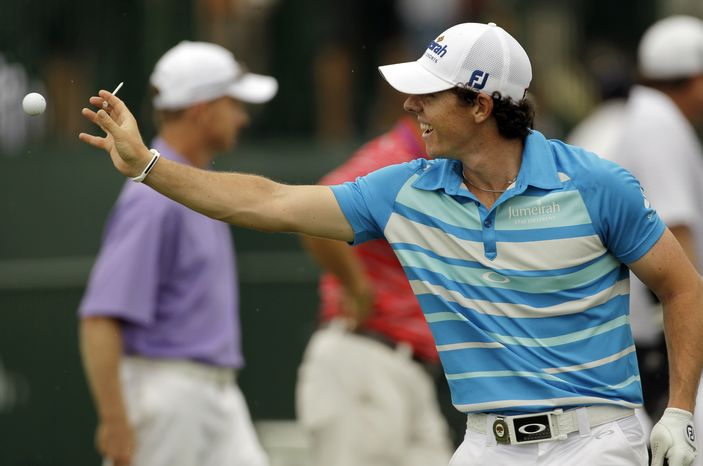 Rory McIlroy of Northern Ireland, reaches for a tossed ball on the driving range during a practice round for the PGA Championship golf tournament on the Ocean Course of the Kiawah Island Golf Resort in Kiawah Island, S.C., Wednesday, Aug. 8, 2012. (AP Photo/Chuck Burton)