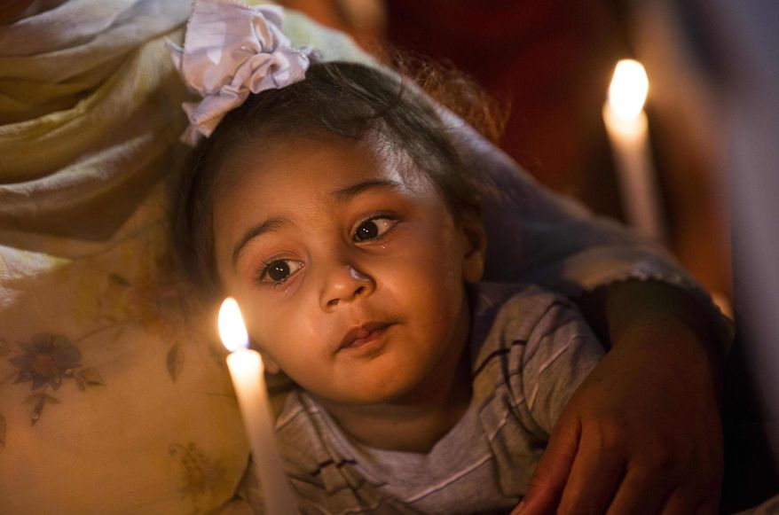 A child is held Tuesday Aug. 7, 2012, in Oak Creek, Wis., at a candle light vigil for the victims of a mass shooting at the Sikh Temple of Wisconsin on Sunday. The vigil was held during the national night out event at the Oak Creek Civic Center. (AP Photo/Tom Lynn)
