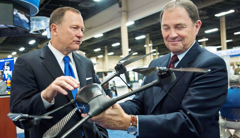 Lockheed Martin Vice President for Ship and Aviation Systems Dan Schultz (left) shows a mini unmanned aerial vehicle, the Quad Vertical Take Off and Landing System, to Utah Gov. Gary R. Herbert at the Associ